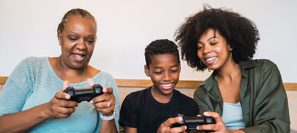 Grandmother, mother and son playing video games at home after taking funeral insurance.