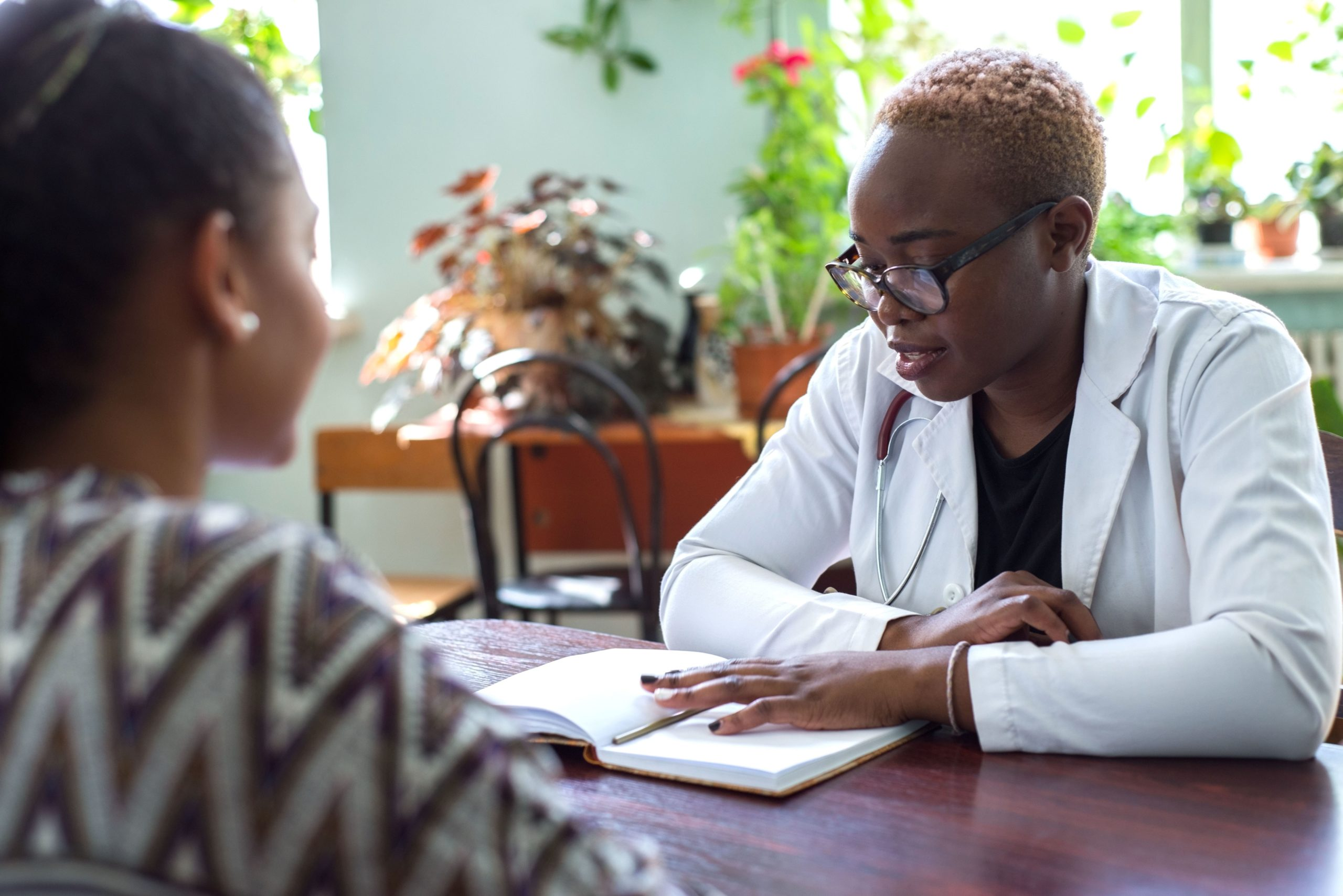 A woman consults a doctor in a white lab coat about the results of her COVID-19 test. Whatever happens next, she can rest at ease, knowing her funeral insurance cover will pay-out to her family if she succumbs to the coronavirus.
