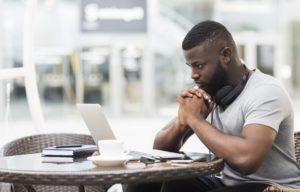 A man sits at a table and is using his laptop to apply for funeral insurance cover. He is considering how long the waiting period for his funeral cover plan will be and whether this insurer offers funeral cover with no waiting period.
