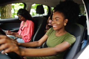 A young woman is driving her friends in her car. Being out and about gets easier when you have an extended motor warranty behind the wheel with you.